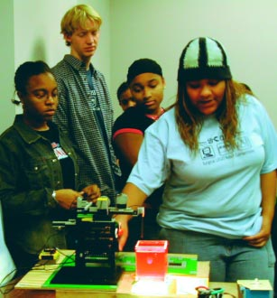 """In a surgical simulation, high school students test their LEGO robot by targeting a """"tumor"""" (a grape plays the part, embedded in Jell-O)."""