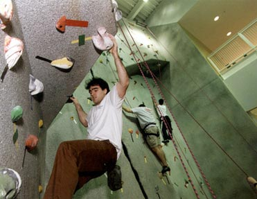 A student scales the 30-foot climbing wall at the Ralph S. O'Connor Recreation Center. Dedicated in April, the center was designed by Sasaki Associates and constructed by the Whiting-Turner Contracting Company. The new facility's Robert H. Scott Gymnasium has a 1/10-mile jogging track that circles above the three courts for basketball, five for volleyball, and three for badminton.