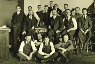 Flanking a sign being ignored by one pipe smoker, professors Carl Clapp Thomas and Alexander Graham Christie (mustache) gather with the Class of 1917 Mechanical Engineering students.