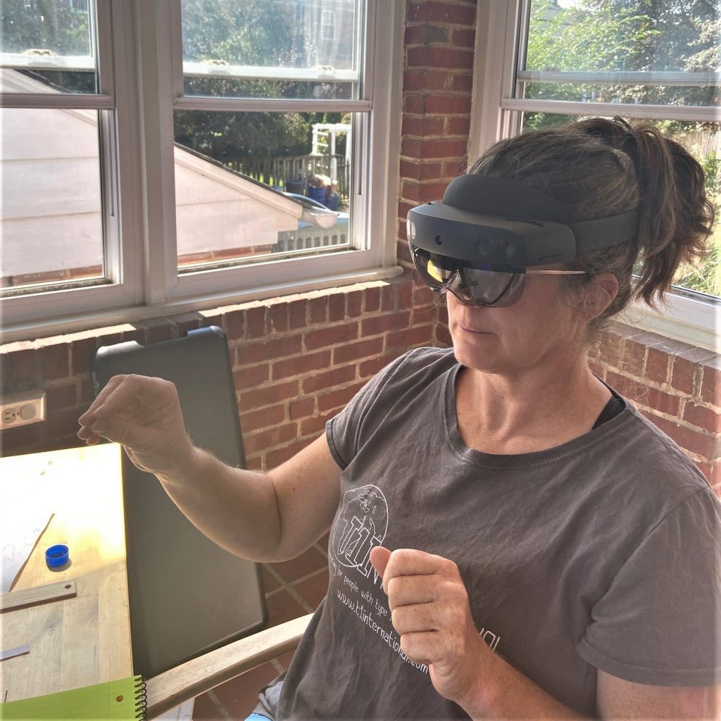 Orla is wearing the smartglasses which wrap around her head. She holds her hands up as she is viewing and manipulating something in mixed reality, only visible to her.