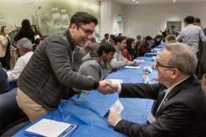 Two people shake hands at a speed networking and recruitment event