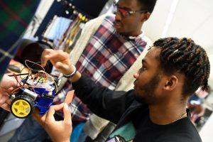 Two Johns Hopkins undergraduates work on a robot