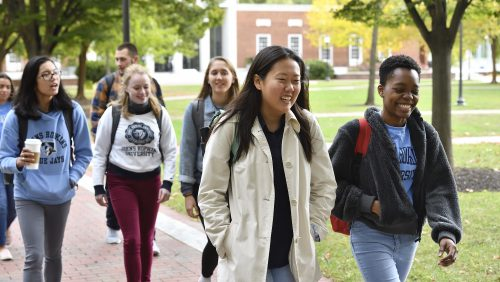 Seven Johns Hopkins students walk on a brick pathway on their way to class