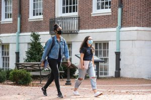Two students wearing masks walk on a brick pathway on Johns Hopkins University's Homewood campus