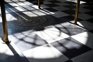 Light casts a shadow over the Johns Hopkins seal in Gilman Hall